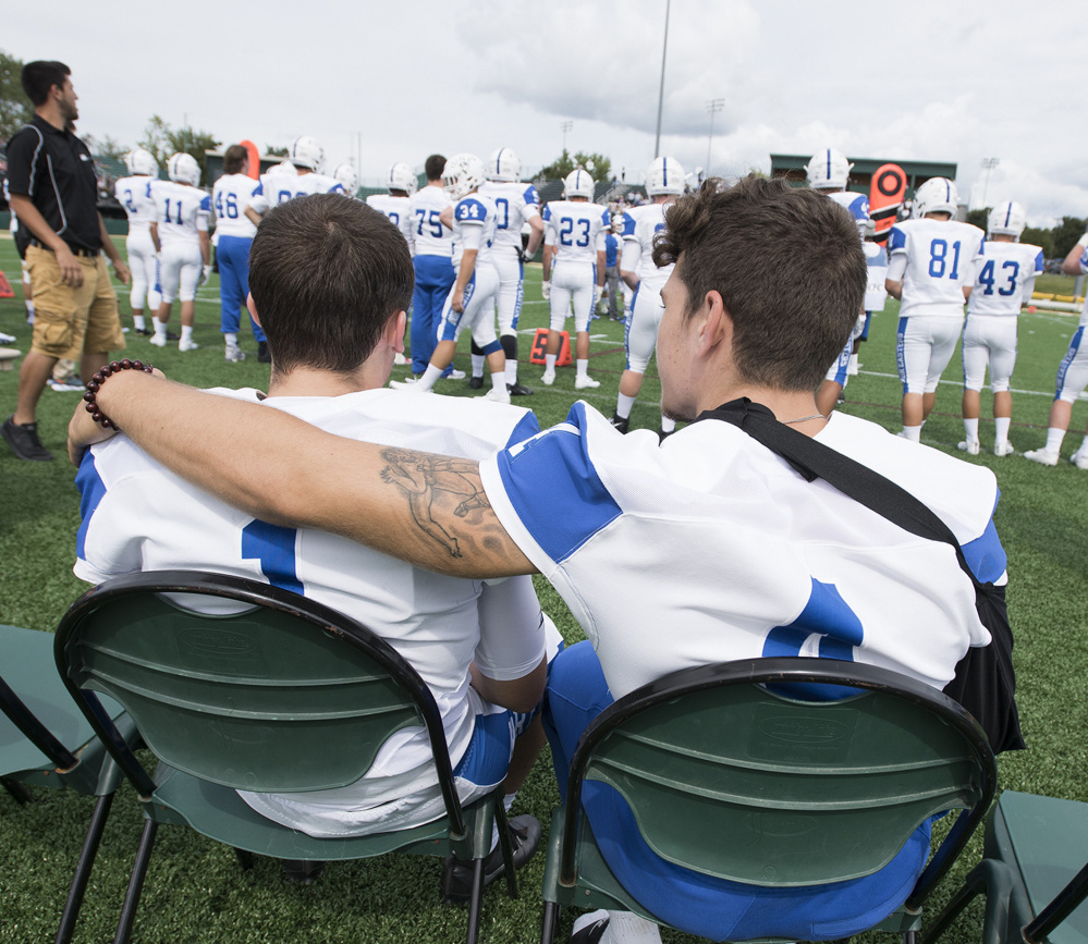 Defensive back Joey Curit, left, of Biddeford shares a moment with linebacker Michael Tuzzo during Sunday's game. Curit and Tuzzo are among the 55 freshman on UNE's roster.