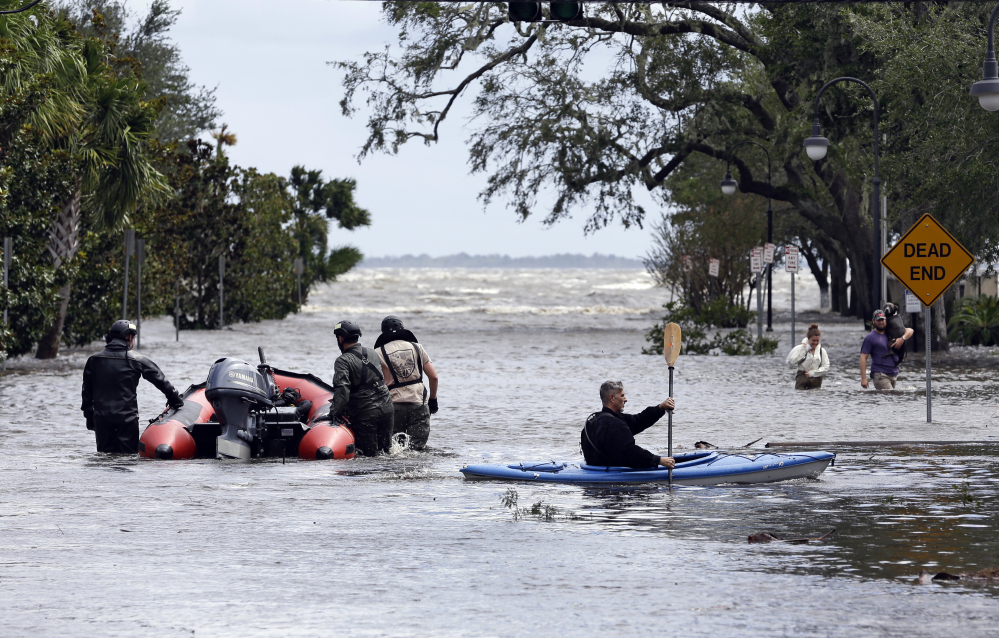 Rescue workers search a neighborhood for flood victims Monday as a man on a kayak paddles down the street after Hurricane Irma brought flood waters to Jacksonville, Fla.