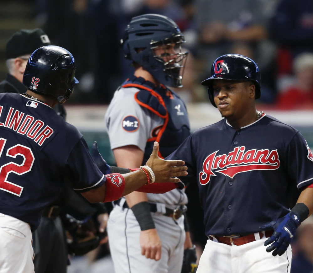 Cleveland's Jose Ramirez gets congratulations from Francisco Lindor, left, after hitting a two-run home run off Detroit starting pitcher Myles Jaye as catcher James McCann stands in the background during the Indians' 11-0 win Monday in Cleveland.