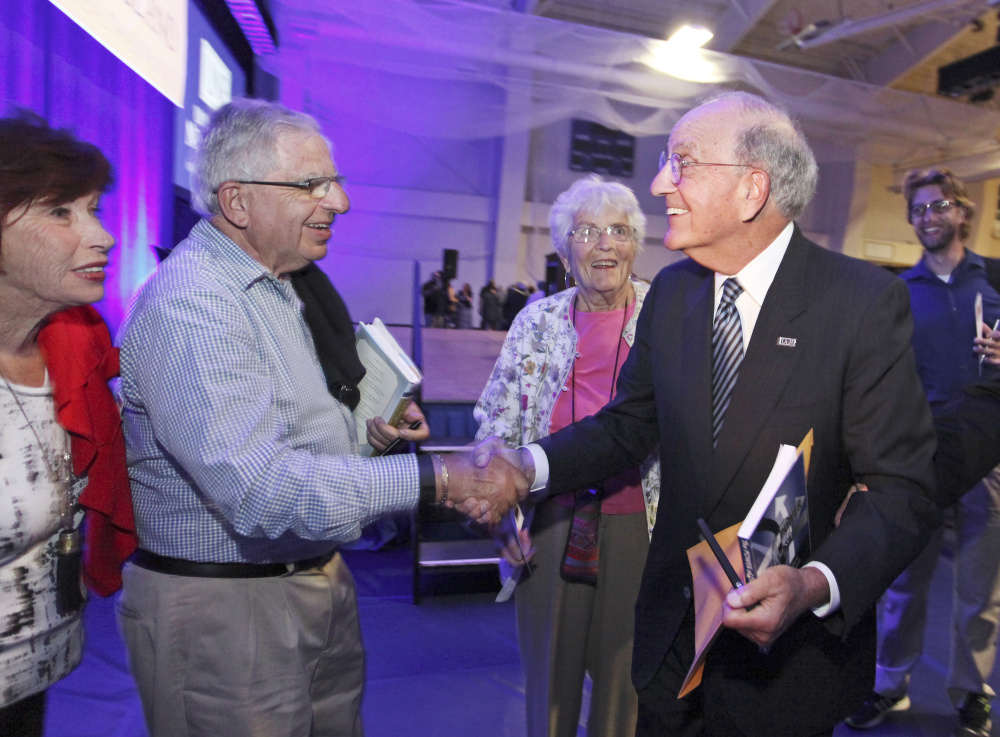Former U.S. Sen. George Mitchell, right, greets Victor Forsley, of Biddeford, and Betty Forsley, far left, after his speech Tuesday at the University of New England in Biddeford.