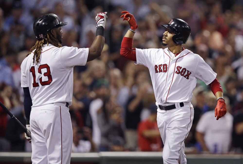 Boston's Mookie Betts, right, is congratulated by Hanley Ramirez after his two-run homer during the fourth inning of Tuesday night's rout of the Oakland Athletics at Fenway Park.