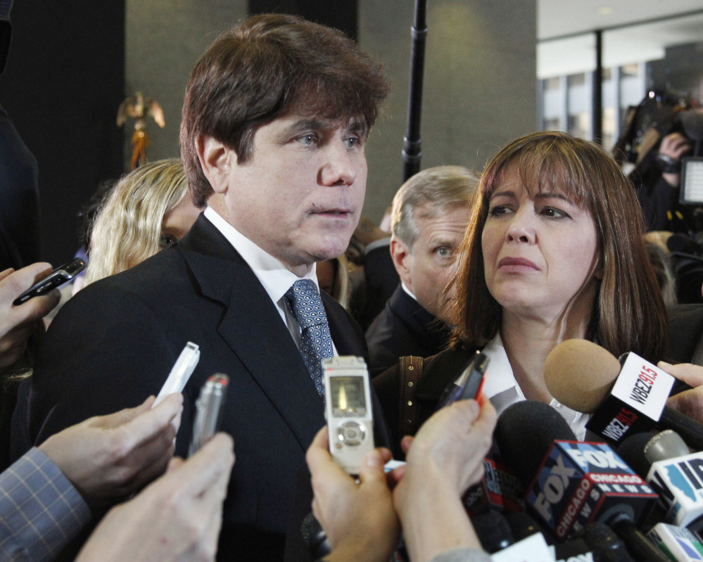 Former Illinois Gov. Rod Blagojevich, speaks to reporters as his wife, Patti, listens in Chicago in 2011. Blagojevich said he spends his time mopping floors while serving a federal sentence after corruption convictions. In a recent interview from a Colorado prison, he still maintains his innocence. Associated Press