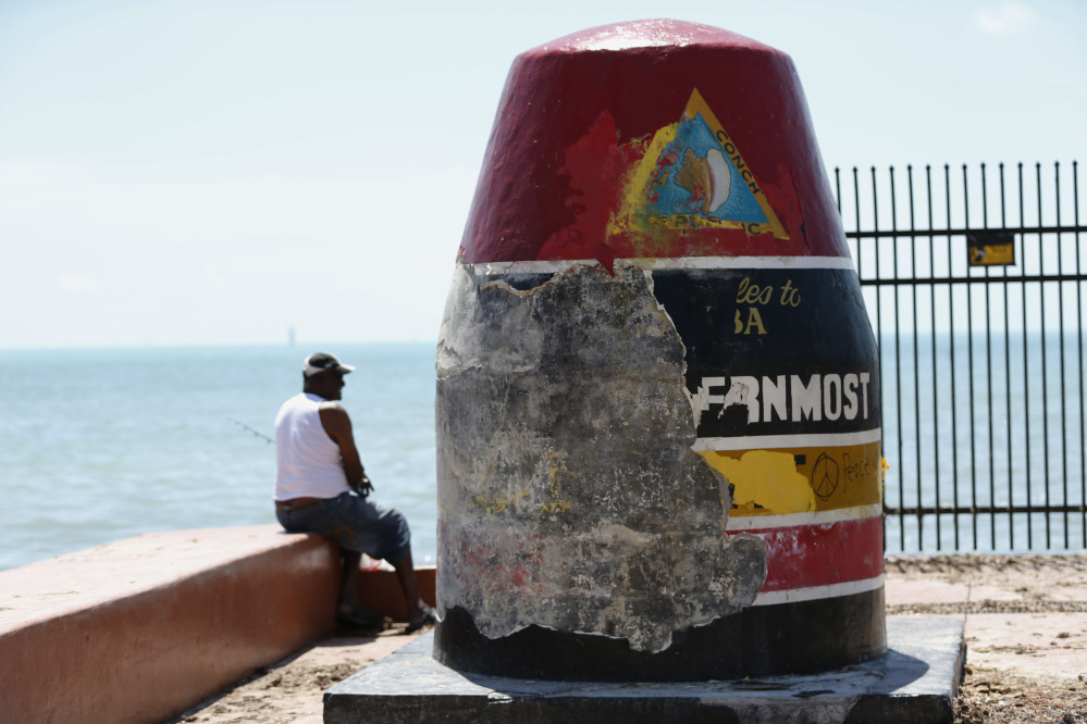 A man fishes Wednesday next to Key West's Southernmost Point Buoy, which shows damage done by Hurricane Irma.