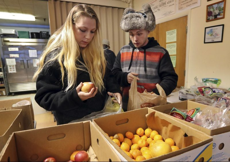 Sunny Larson, left, and Zak McCutcheon pick produce while gathering provisions to take home from the Augusta Food Bank, which is serving a record-breaking number of families – over 400 a month. Food pantries have become a regular source of nutrition for many, not just a stopgap.