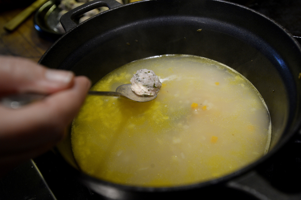 Christine Burns Rudalevige lowers a meatball into broth while cooking a meatball soup with fermented herbs.