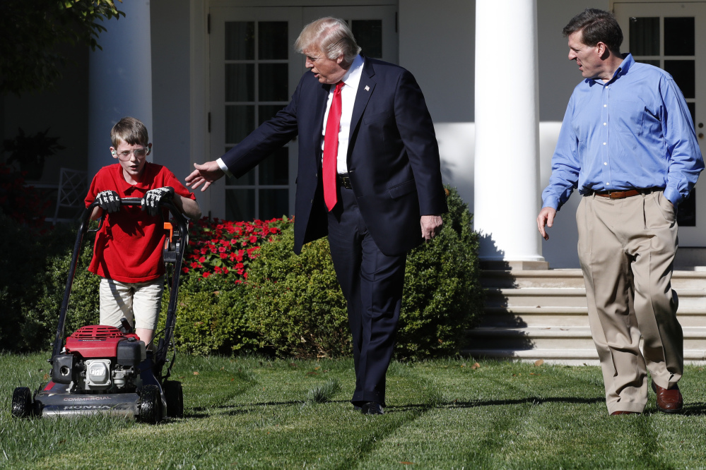 Frank Giaccio, 11, of Falls Church, Va., left, is accompanied by President Trump as he mows the lawn of the Rose Garden, Friday at the White House with his father Greg Giaccio.