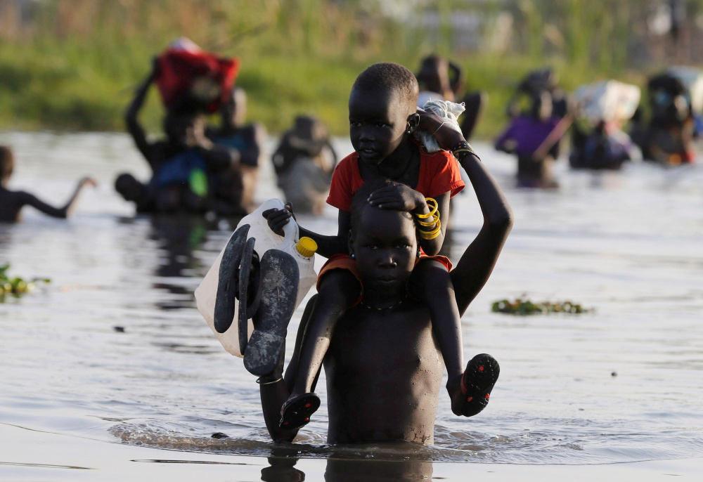 Children cross a body of water to reach a registration area prior to a food distribution carried out by the United Nations World Food Programme in South Sudan in February.
