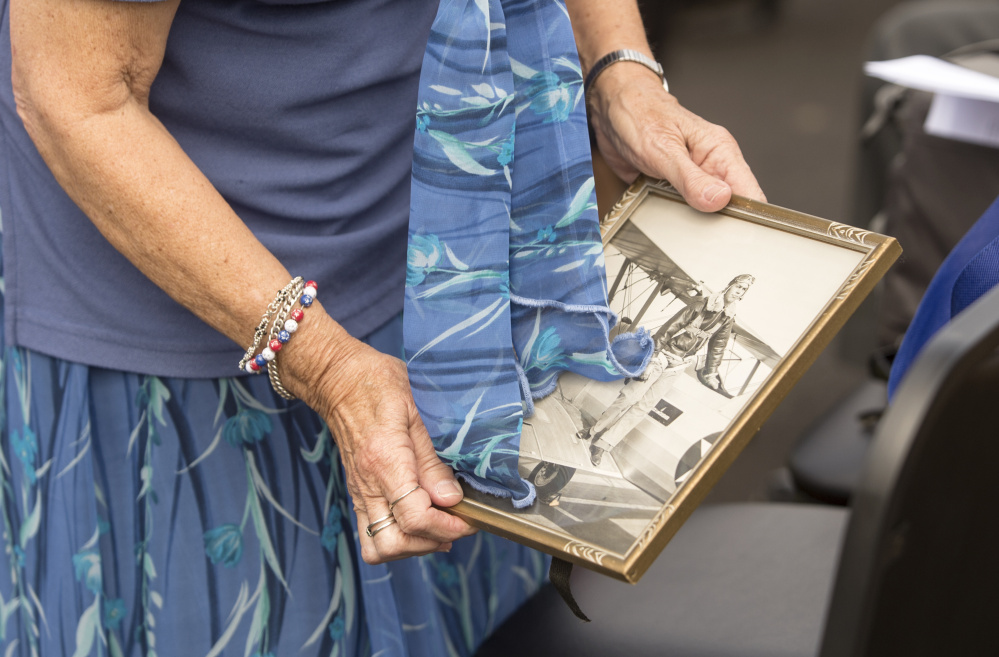 Norma Spurling holds a framed picture of her brother George Hout on Friday during the ceremony in Winslow.