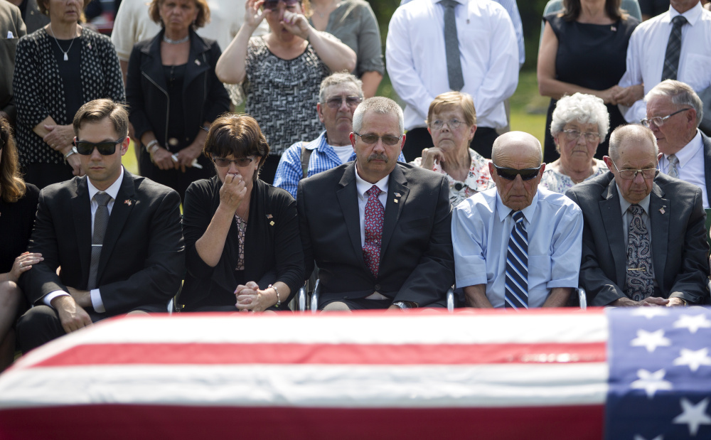 From left, Capt. Ben Cross' brother, Ryan Cross, his  mother, Valerie Cross, and his father, Robert Cross, along with other family members gather in front of Ben Cross' casket as he is laid to rest. Ryan Cross told the Press Herald the family has not received a call or letter from President Trump.