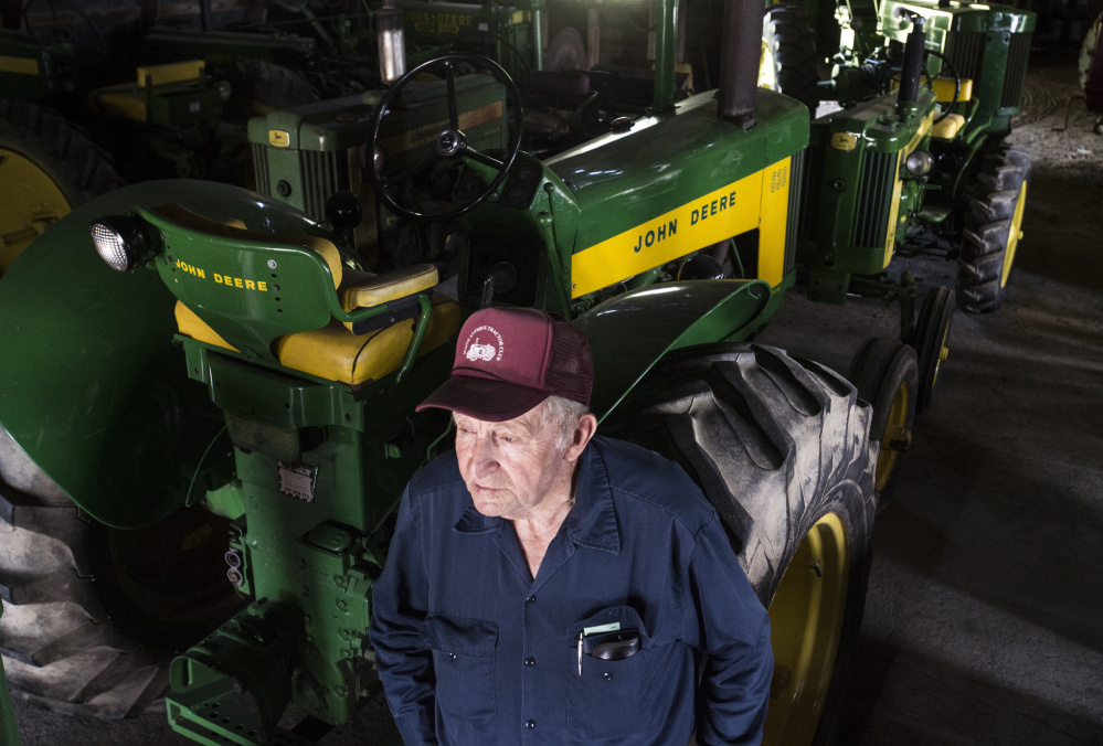 Bill Clark, a charter member of the Maine Antique Tractor Club, stands with his nearly 40 John Deere tractors Thursday in his Skowhegan barn.
