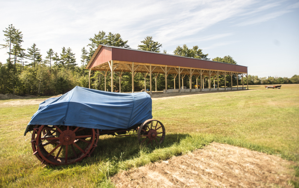 An antique tractor protected by a tarp stands at the Maine Antique Tractor Club in Norridgewock next to the new tractor-pull building built by an Amish construction company.