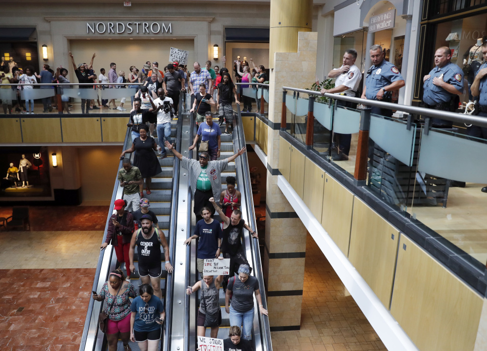 Protesters march through a mall in response to an acquittal in the trial of former St. Louis police officer Jason Stockley as police stand by Saturday in Des Peres, Mo.