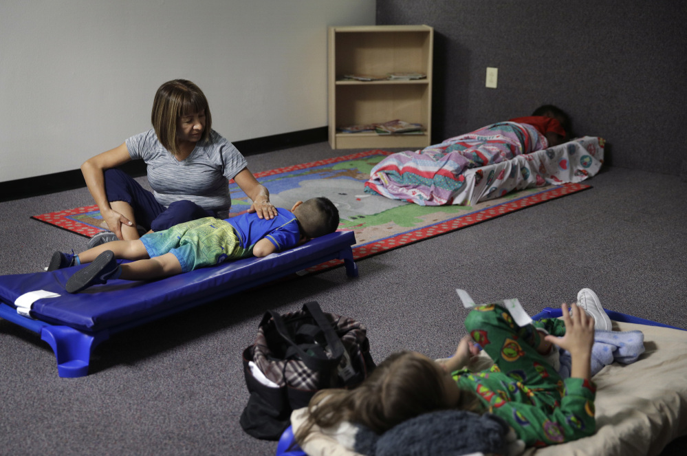 Hortencia Hansen helps a child go to sleep during bedtime at the McCarran International Child Development Center, a 24-hour daycare in Las Vegas. Those who work outside of the 9-to-5 shift are lost in the national conversation over access to child care and early education. It's true even in Las Vegas, which has the rare offering of 24-hour daycares.