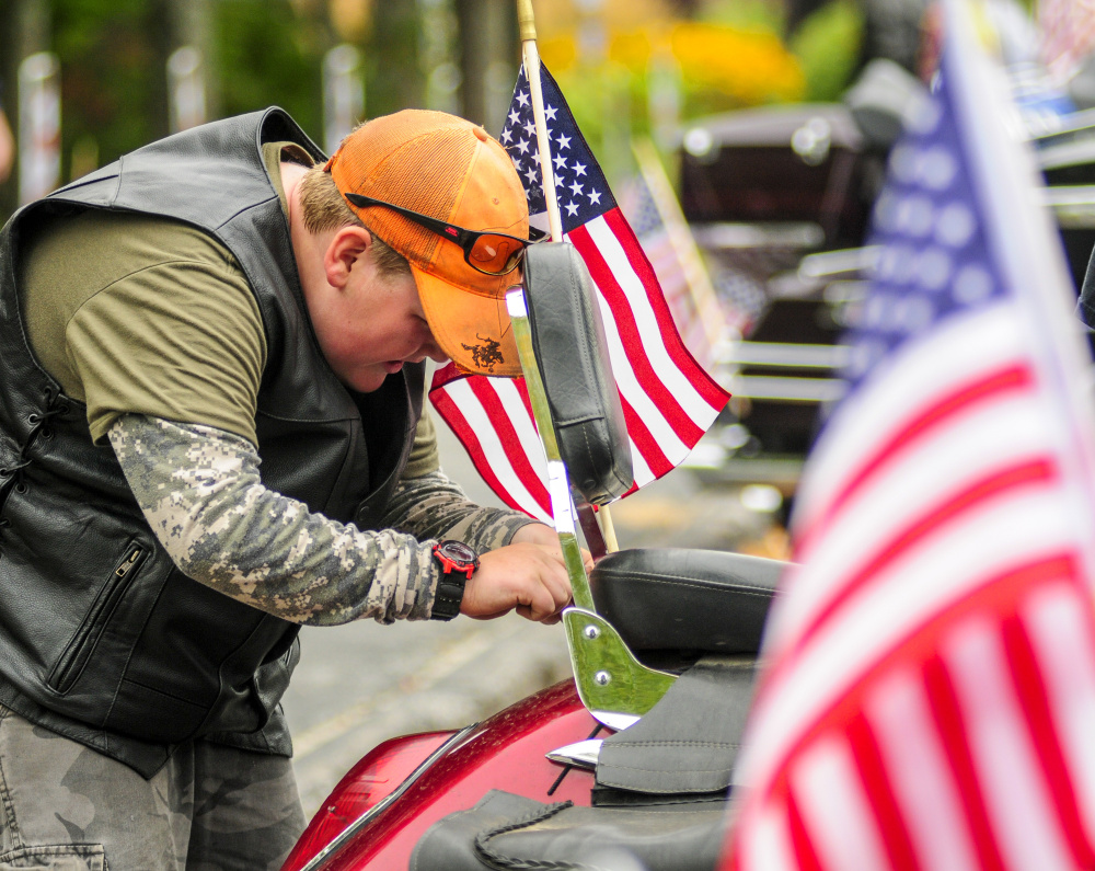 Coleby Monteith, 11, of Randolph, attaches an American flag to his grandfather's motorcycle Saturday before they rode in the 2017 Maine Fallen Heroes Bike Run at the Maine Veterans' Home in Augusta.