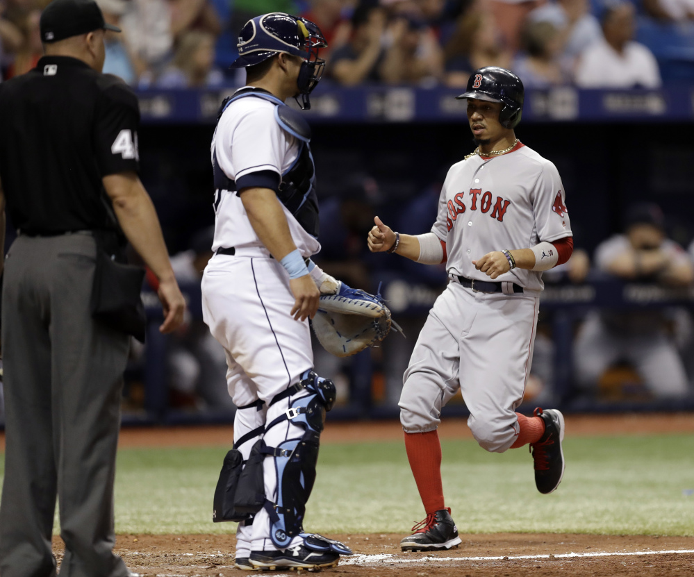 Boston's Mookie Betts scores in front of Tampa Bay Rays catcher Wilson Ramos and home plate umpire Jeff Nelson on a double by Rafael Devers during the sixth inning of Saturday's game in St. Petersburg, Fla. The Red Sox won, 3-1.