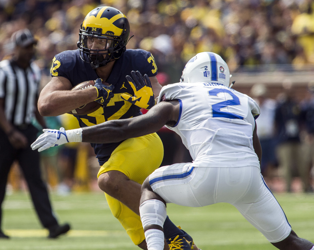 Ty Isaac of Michigan attempts to run past Marquis Griffin of Air Force during the second quarter of Michigan's 29-13 victory Saturday. The seventh-ranked Wolverines improved to 3-0 and dropped the Falcons to 1-1.