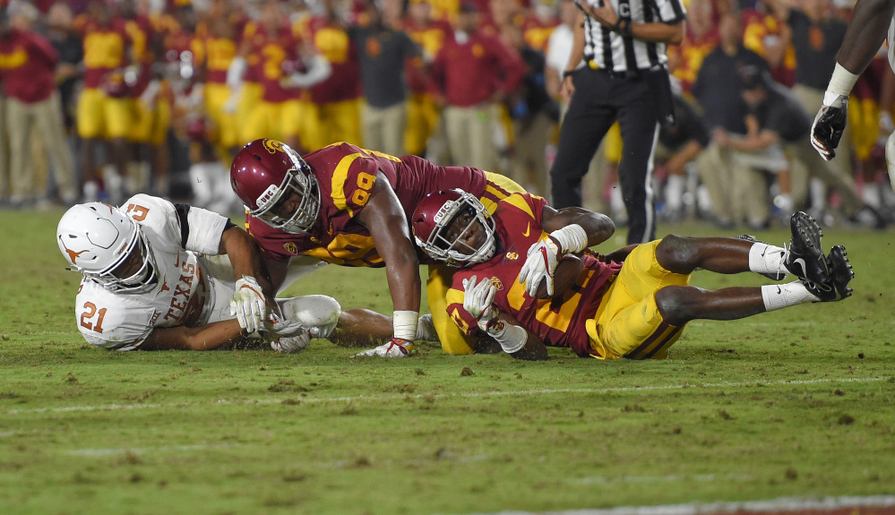 USC cornerback Ajene Harris, right, recovers a fumble by Texas as Texas running back Kyle Porter, left, and defensive lineman Christian Rector fall during the second overtime Saturday night in Los Angeles. USC won 27-24 in two overtimes.