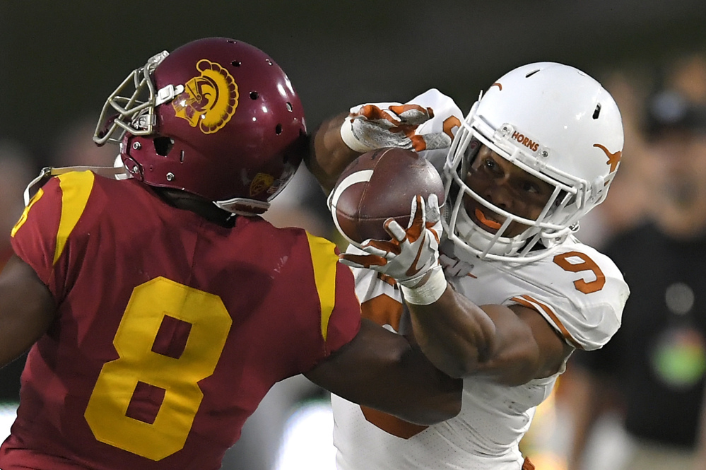 Texas wide receiver Collin Johnson catches a pass as USC cornerback Iman Marshall defends.