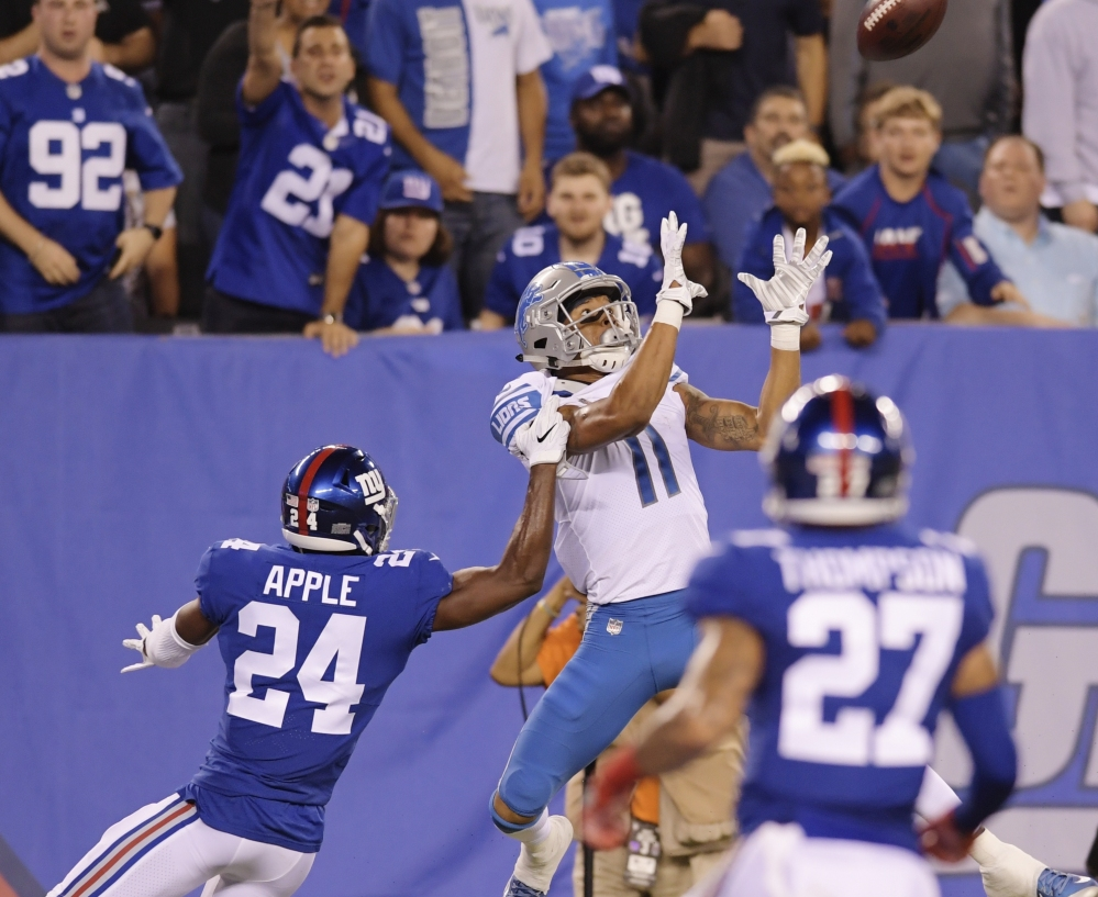 Marvin Jones of the Lions leaps to catch a touchdown pass against Eli Apple of the Giants during Monday's game in East Rutherford, N.J.