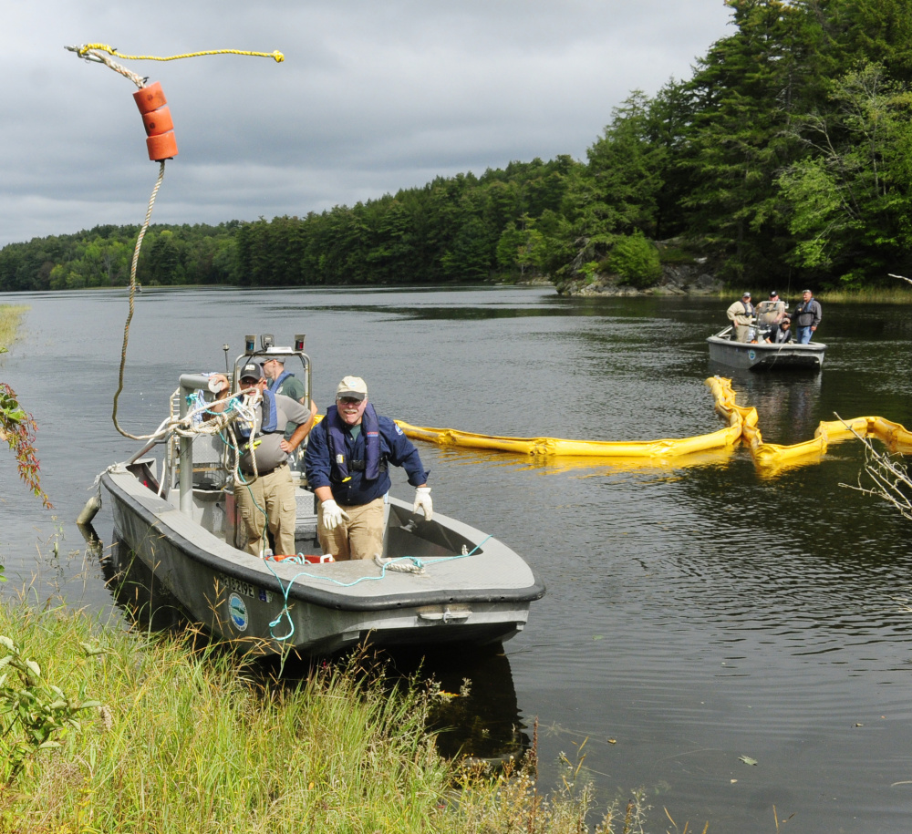 Department of Environmental Protection Division of Response Services staffer Robert Williams, center, tosses the line from a containment boom to a co-worker on shore on Tuesday during a training exercise in the Kennebec River off Swan Island.