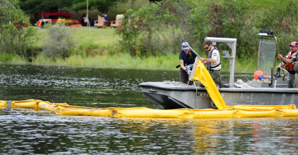 Tiffany LaClair, of the Dept. of Environmental Protection's Division of Response Services, left, and John Pratte, biologist for the Dept. of Inland Fisheries & Wildlife, pull the end of a containment boom Tuesday during a training exercise in the Kennebec River off Swan Island.