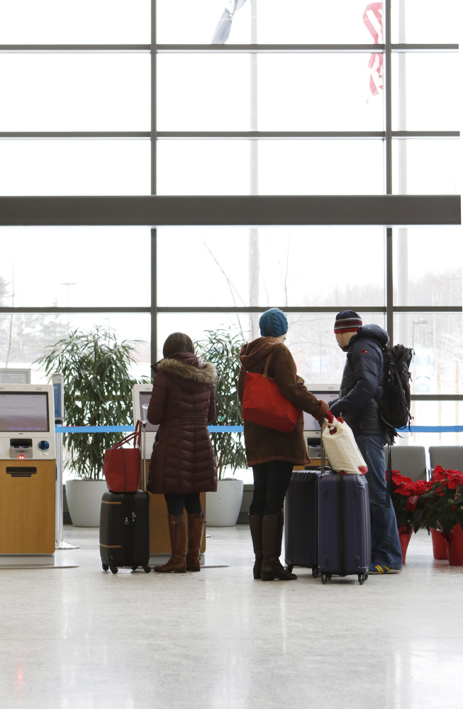Travelers check in for flights at the Portland International Jetport in 2015. Airlines collected nearly $1.2 billion in checked bag fees during the second quarter of this year – a new record.