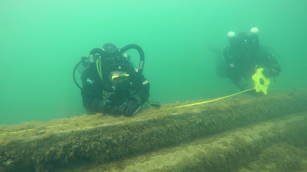 Maritime archaeologists and volunteers measure the keelson of the J.M. Allmendinger, which sank in 1895 in Lake Michigan near Port Washington, Wis. At left, shipwreck enthusiast Steve Radovan of Sheboygan, Wis., stows a sonar transducer on his boat in Lake Michigan during a survey of underwater shipwrecks. A marine sanctuary is proposed for the site. (