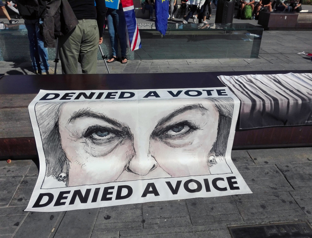 A poster showing British Prime Minister Theresa May is displayed during a protest staged by a group of U.K. citizens living in Italy, in Florence, Italy, on Friday.
