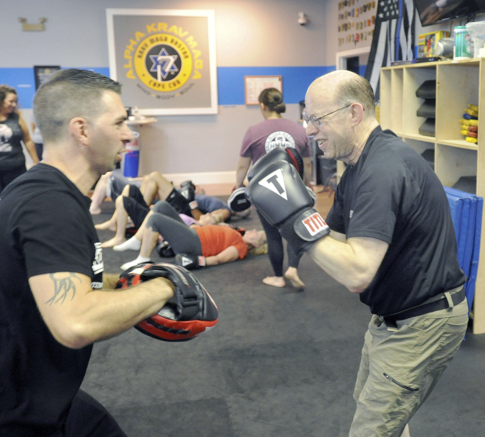 Jeff Wahtola, left, of Hyannis Mixed Martial Arts works with Manny Mason of Cotuit, who has Parkinson's disease, at the Alpha Krav Maga gym.