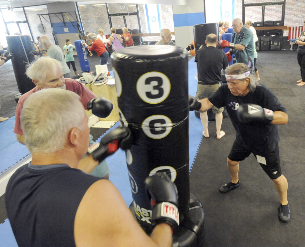 Jay Zavala of Falmouth, Mass., right, Ralph Tomasian of West Barnstable, left, and Charlie Tempinski of Marstons Mills work out in a Rock Steady class in Hyannis. The boxing program is designed to counter symptoms of Parkinson's disease.