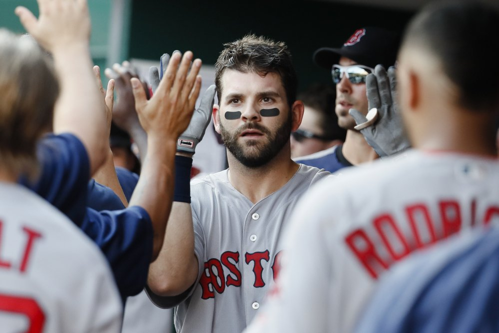 Boston's Mitch Moreland celebrates in the dugout after hitting a three-run homer off Cincinnati's Robert Stephenson in the sixth inning of Saturday's game in Cincinnati. The Red Sox won, 5-0.