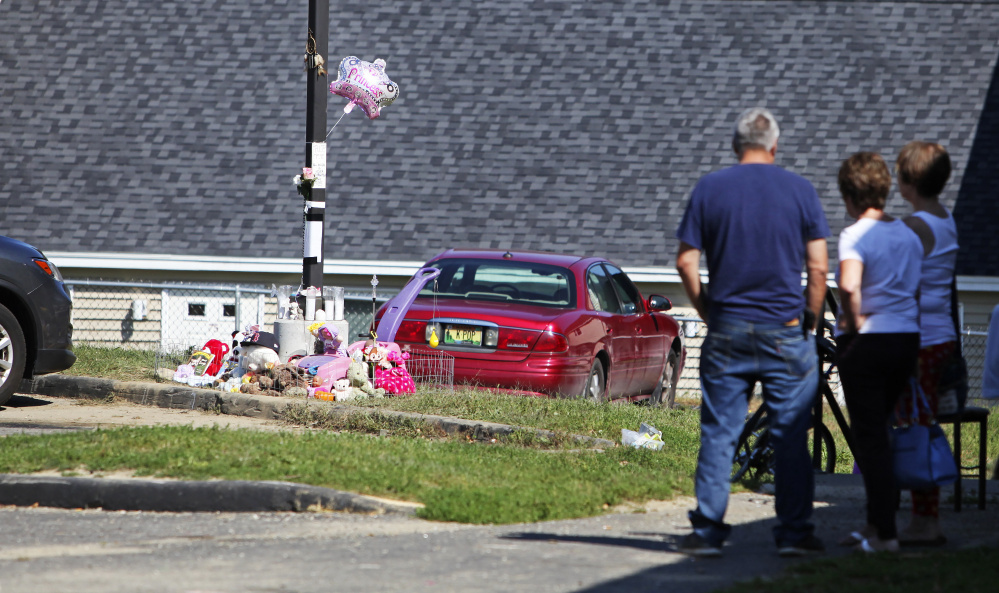 Neighbors gather Sunday in Lewiston near a memorial for 17-month-old Tiannah Sevey, who was killed Saturday when her mother, Taneisha Thomas, ran over her. Police say it's unlikely the woman will be charged.