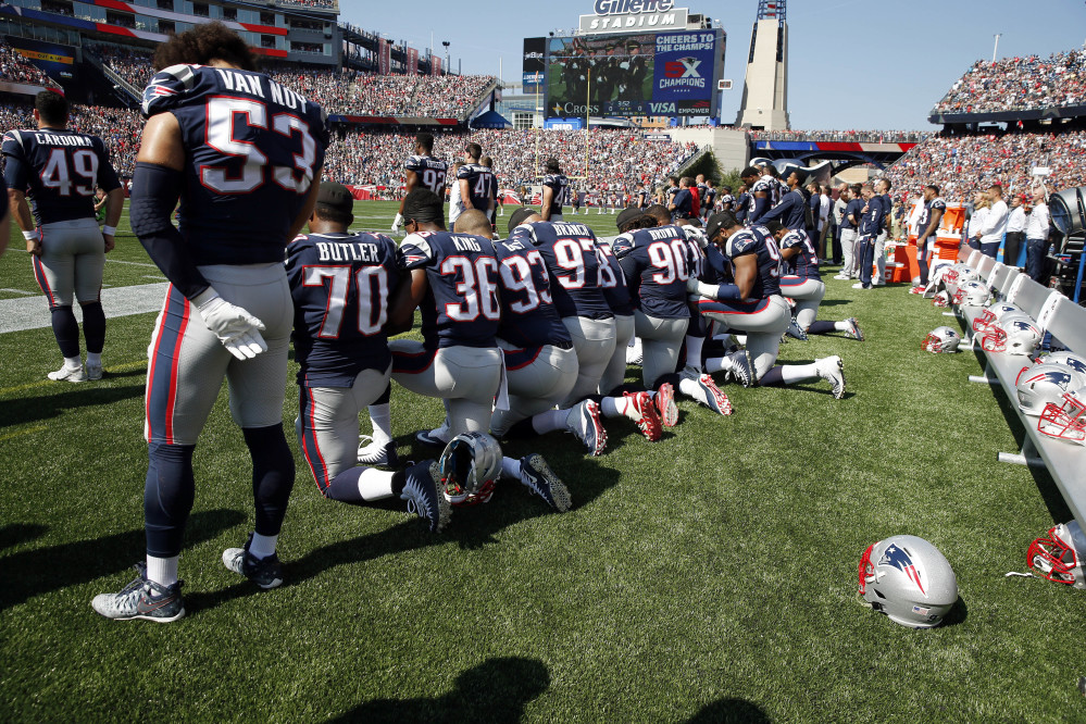 Several New England Patriots players kneel during the national anthem before Sunday's game.