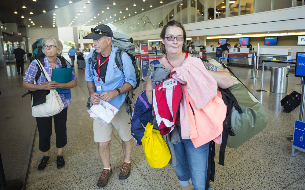 Red Cross volunteers Anne Heminway of Phippsburg, left, Jim Kerrigan of Old Orchard Beach and Crystal Abbott of Alfred arrive at the Portland International Jetport on Monday before flying to Atlanta ahead of their deployment to Puerto Rico.