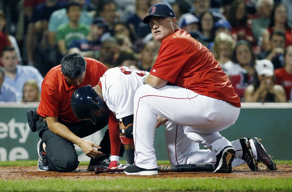 Red Sox manager John Farrell, right, and a trainer tend to Eduardo Nunez in the third inning Monday night. Nunez aggravated a right knee injury and was removed from the game after finishing his at-bat.