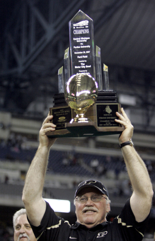 FILE - In this Dec. 26, 2007, file phoot, Purdue head football coach Joe Tiller holds up the winning trophy after defeating Central Michigan 51-48 to win the Motor City Bowl NCAA college football game in Detroit.  Tiller, the winningest football coach in Purdue history, died Saturday, Sept. 30, 2017, in Buffalo, Wyo., the school said. He was 74. (Associated Press/Carlos Osorio)