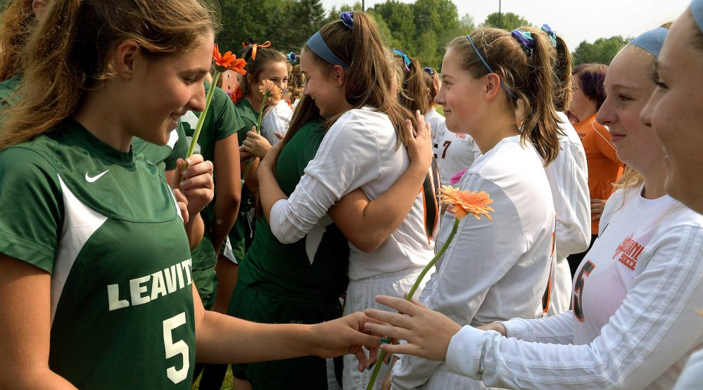 Leavitt soccer players, left, hand Gardiner players flowers before a Class B game Tuesday in Gardiner. It was the first game the Tigers played since teammate Taby Hembree died from injuries sustained in a car accident last Thursday.
