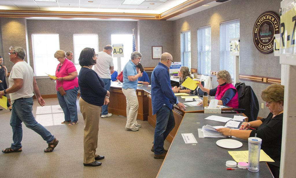 In Tuesday's referendum on the school budget, Scarborough residents pick up ballots before voting at the town hall. Left out of the initial vote count were 420 ballots.