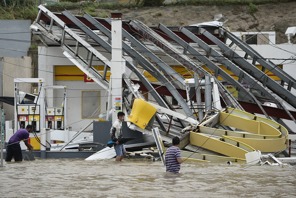 People wade near a gas station in Humacao, in the eastern region of Puerto Rico, on Sept. 20, after Hurricane Maria hit.