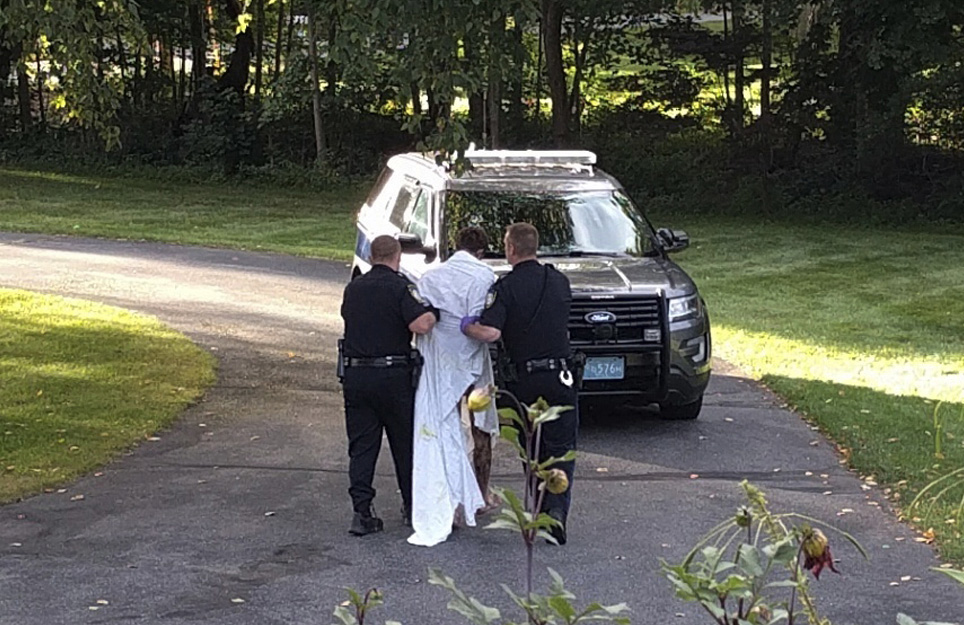 Police officers take Orion Krause, covered in a white sheet, to a police vehicle in Groton, Mass., on Friday.