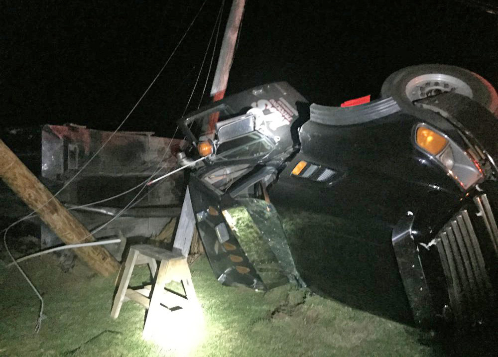 A dump truck lies on its side on Lakeview Drive in China Tuesday night after wires snagged the raised dump bed and tipped the vehicle over.