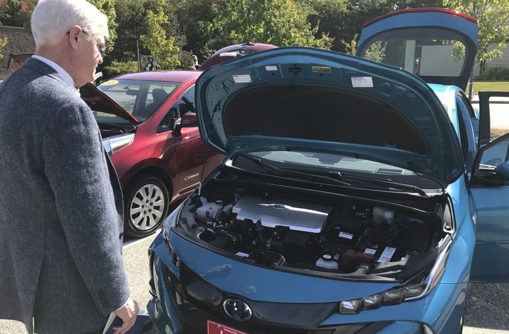 Steve McGrath, director of the governor's energy office, examines the engine on a Toyota Prius Prime on Wednesday, at a seminar in Brunswick on workplace charging stations for electric vehicles.