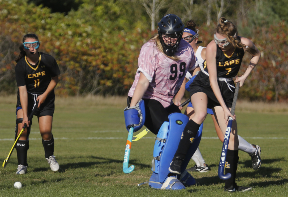 Emi Logue of Cape Elizabeth taps the ball past Old Orchard Beach goalie Leah Green to open the scoring in the first half Wednesday. The visiting Capers went on to a 3-0 victory in the Western Maine Conference field hockey game.