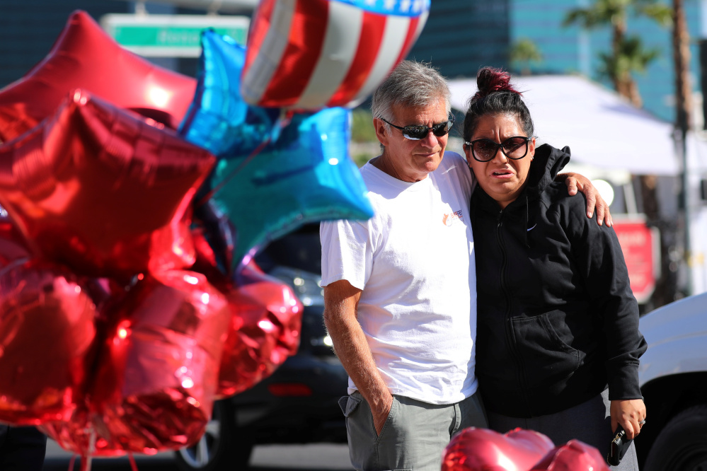 A couple hug after stopping their car to view a makeshift memorial in Las Vegas to the victims of the mass shooting.