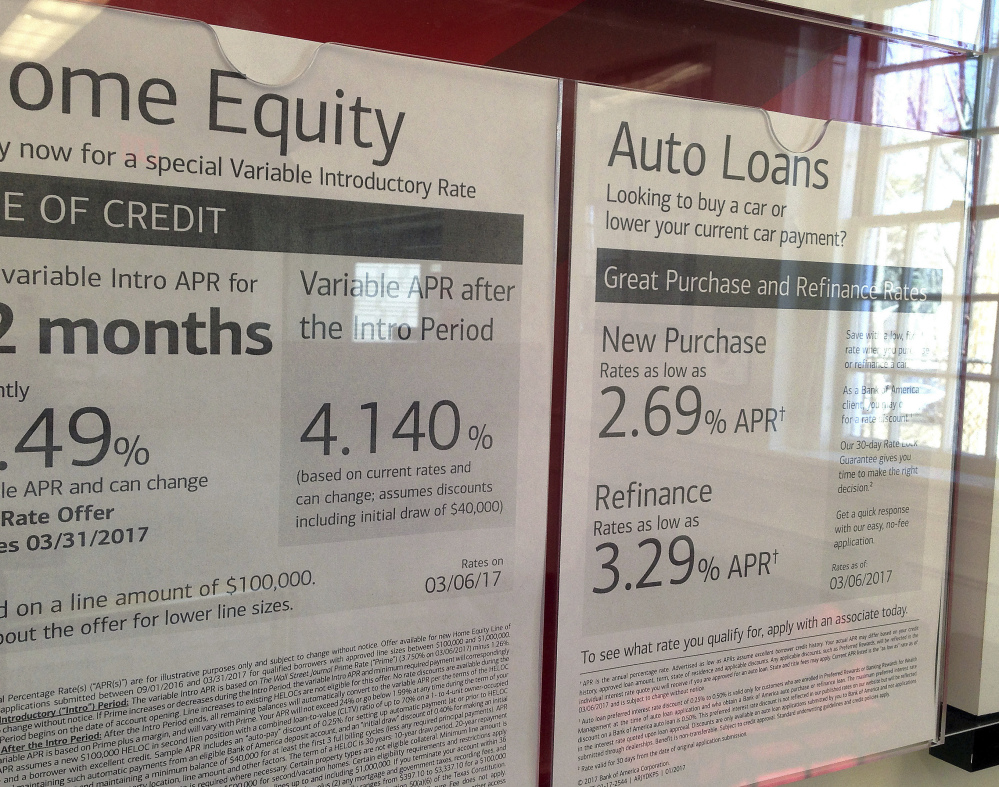 Home equity and auto loan rates are displayed at a bank in North Andover, Mass. Consumer borrowing slowed in August.