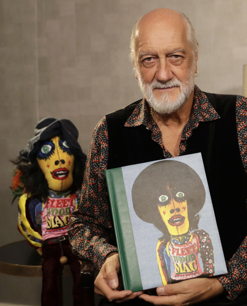 Mick Fleetwood holds a copy of