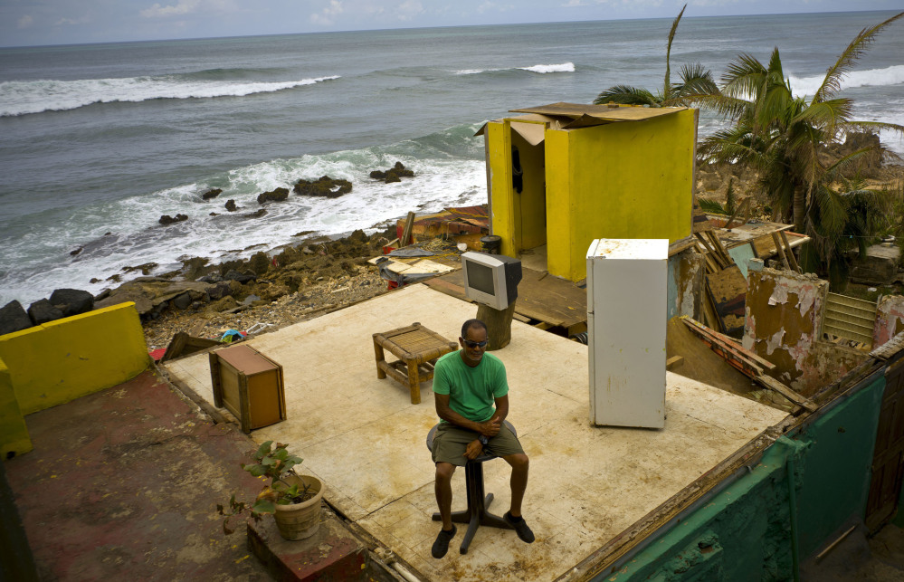 Roberto Figueroa Caballero sits on a small table at the remains of his San Juan, Puerto Rican, home that was destroyed by Hurricane Maria last month.
