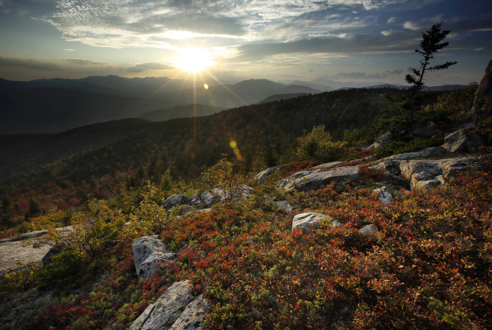 The sun begins to set in this view from South Moat Mountain in Albany, N.H. Longtime leaf watchers say the leaves this fall are dull and weeks behind schedule in reaching their peak.