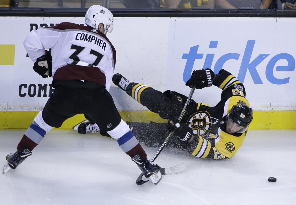 Colorado left wing J.T. Compher, left, and Boston left wing Brad Marchand vie for control of the puck as Marchand hits the ice in the third period Monday in Boston. The Avalanche won 4-0.
