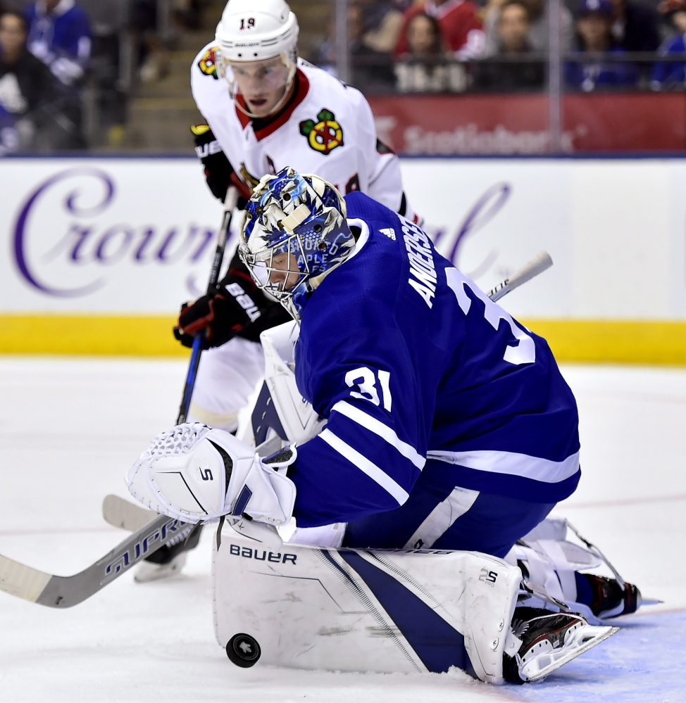 Maple Leafs goalie Frederik Andersen makes a save as Chicago's Jonathan Toews chases the rebound Monday night in Toronto. The Leafs won in overtime, 4-3.